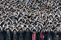 Commencement photo with students in caps and gowns doing O-H-I-O
