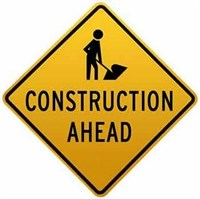 Construction Ahead road sign with outline of workers on a yellow background