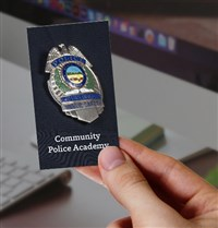 Community Police Academy Ohio State badge with a hand holding it